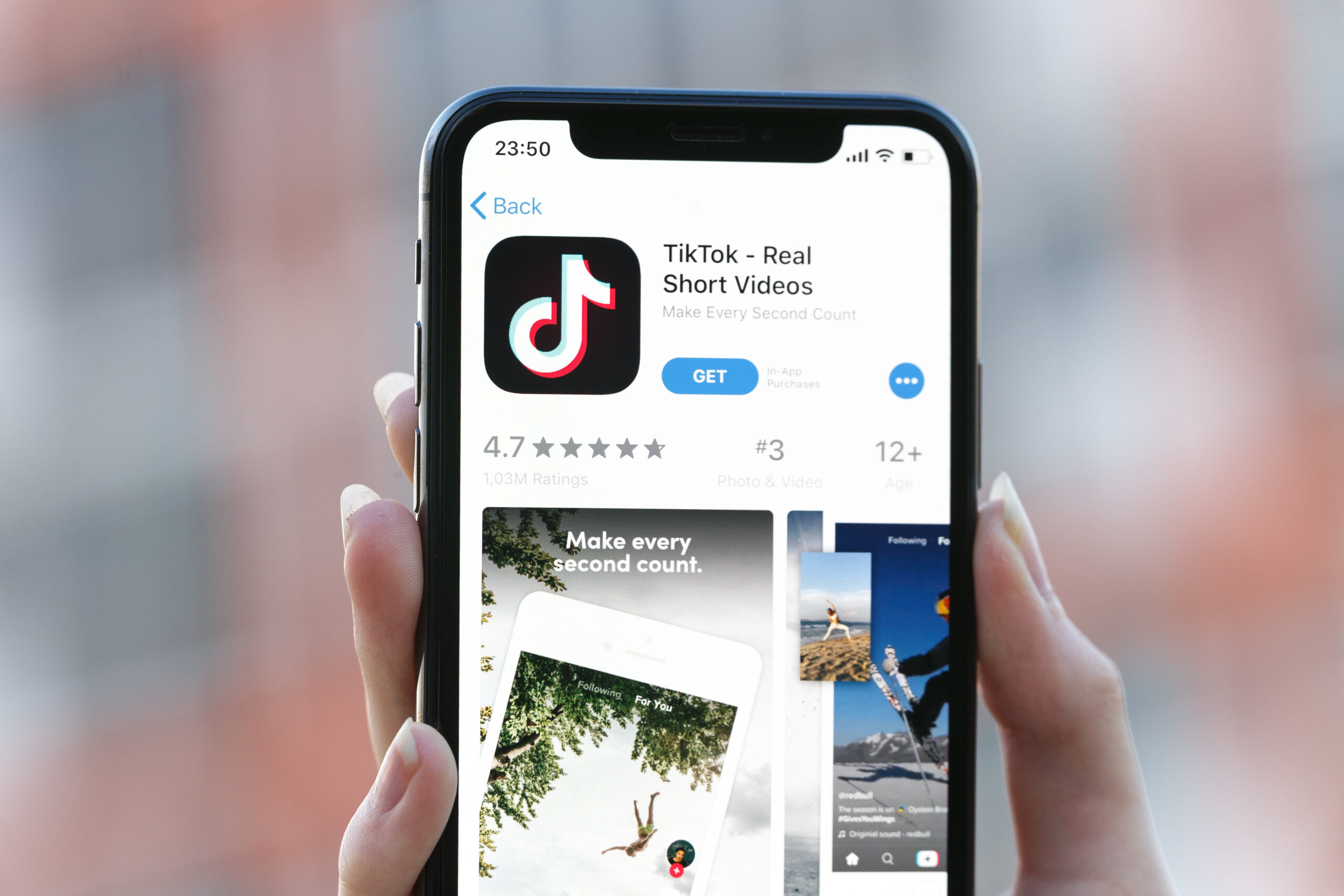Person holds mobile phone showing Tik Tok homepage