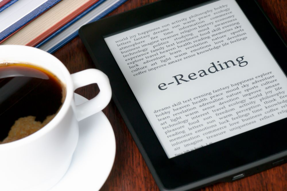 e-reading kindle next to coffee cup