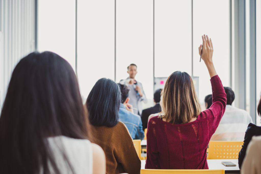 Woman sits with hands up with teacher