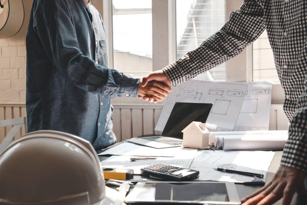 Two businessmen shaking hands over a desk full of paper