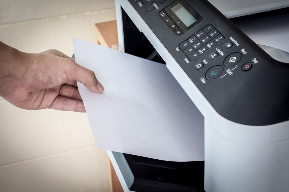 Hand takes a paper from a machine