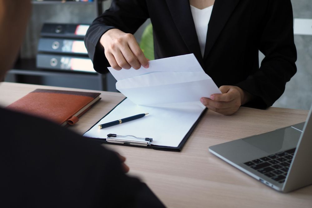 Person handles papers as another sits across table