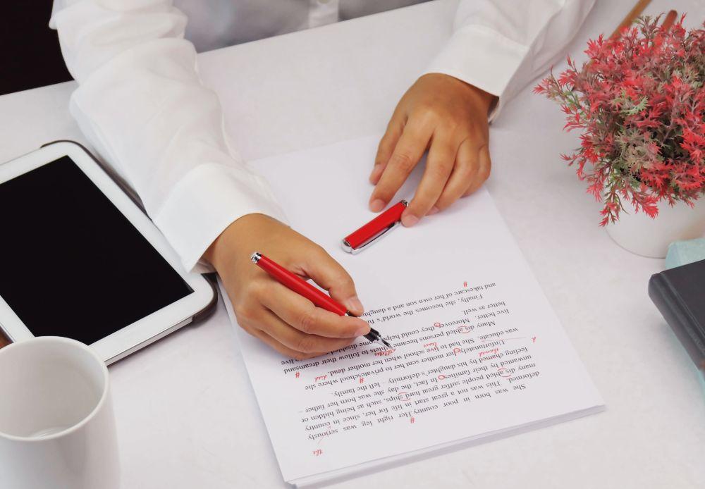 Hands make red marks on paper