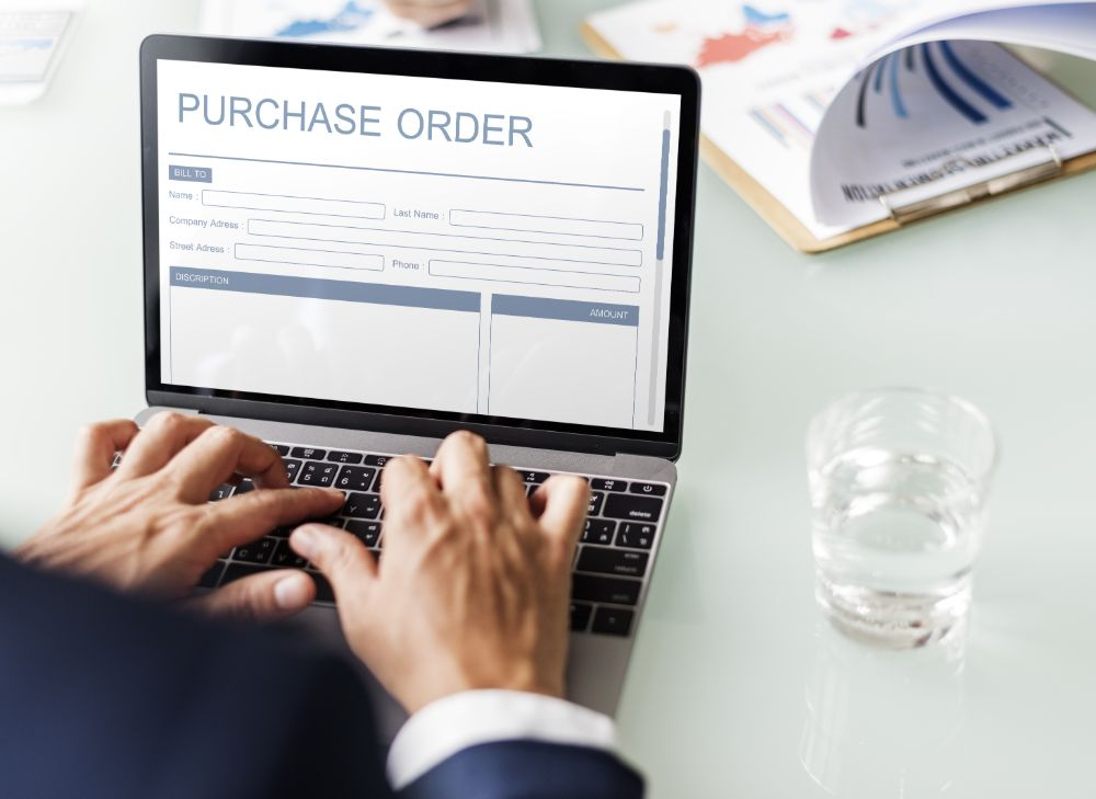 male hands input a purchase order on laptop