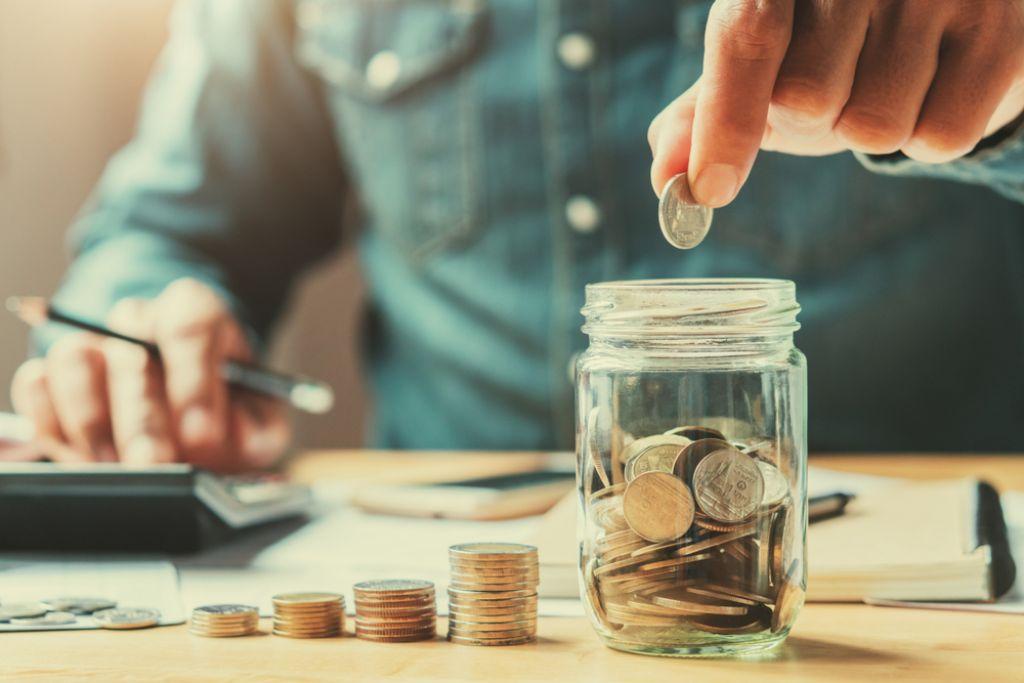 Man putting pennies in the jar